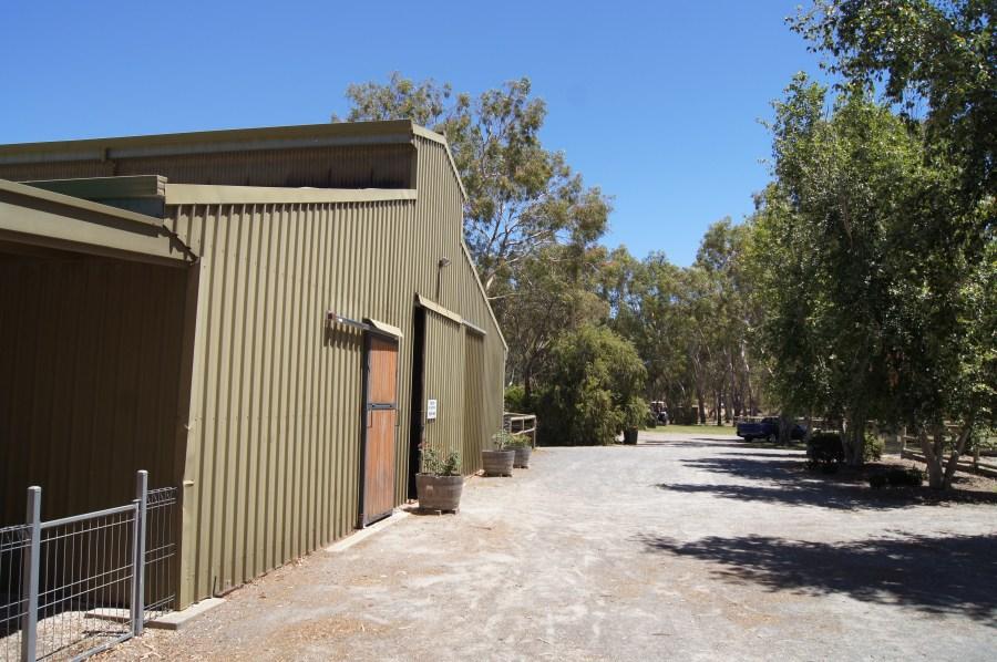 Large parking area adjacent stable entrance.